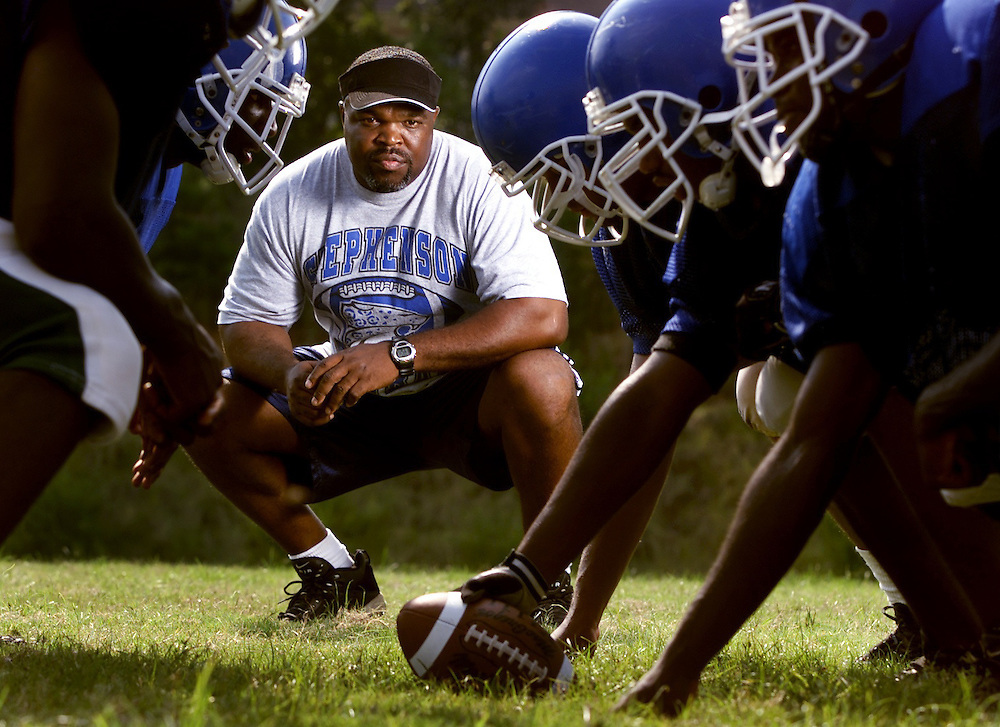 Portrait of Stephenson High School coach Ron Gartrell studying his linemen.