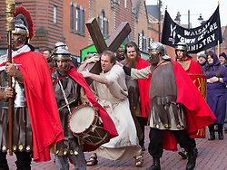 © Licensed to London News Pictures. 30/03/2018. Walsall, UK. The annual Good Friday Walk of Witness taking place in Walsall Town Centre. The Walsall Town Centre Ministry of Churches arranges for actors to portray Jesus being forced by soldiers and paraded through the town centre carrying a wooden cross. The event culminates at the bridge where he is put on the cross in front of the crowd. Photo credit: Dave Warren/LNP