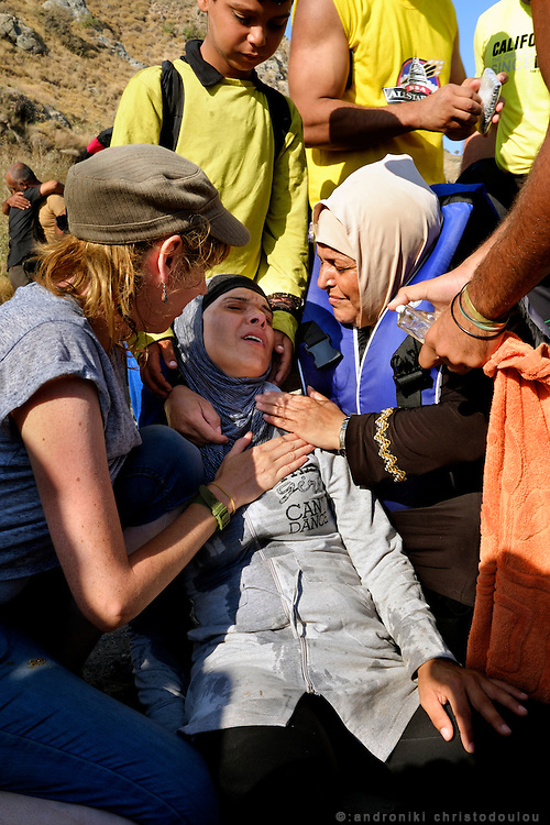 Refugee lady that collapsed dehydrated and shocked after her dangerous trip under the sun, is assisted by an Irish volonteer lady, her son and other refugees. <br /> Refugees arriving on beaches near Molyvos village in Lesvos island. Thousands of them come from Turkey, crossing the sea border on inflatable dinghy boats, on a dangerous trip that has claimed many lives. Local people or NGOs expect them and help them in some places but after their arrival, most of them have to walk to the nearest village where they can hope for a places on busses that can take them to the city of Mytilene where they can register and eventually board on a ferry to Athens. Many decide to walk the distance as the busses aren&rsquo;t enough to accommodate the large number of people that arrive daily.