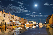 A full moon lights up the sky over Custom House Wharf and Harbor Fish Market in Portland's Old Port.