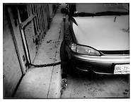Heavy chains fix front wheels of car to house, Tijuana, Baja California, Mexico.  Crime and car theft are indicative of the higher level of poverty south of the border.  Lack of water is a major factor contributing to pervasive poverty south of the border.