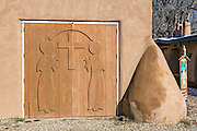 Carved wooden doors on the historic San Francisco de Asis Mission Church in Ranchos de Taos Plaza, Taos, New Mexico. The adobe church built in 1772 and made famous in paintings by artist Georgia O'Keeffe.