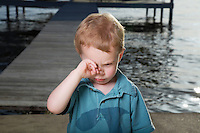 Little Boy on Pier Rubbing His Eyes