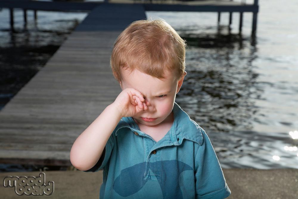 Little Boy on Pier Rubbing His Eyes