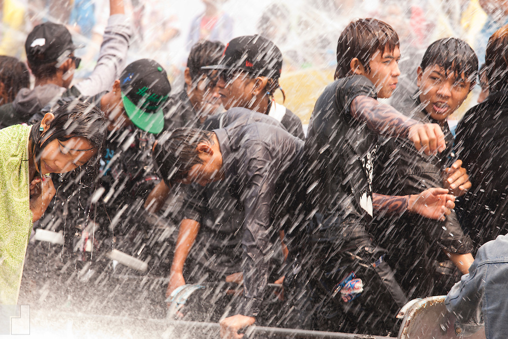 Mandalay, Myanmar- April 14, 2013: Young people climb atop a moving vehicle to dance and get hosed by water during Myanmar's Thingyan Water Festival. Thingyan is held in April, one of the hottest months of the year in Myanmar. The water festival marks the country's New Year celebration and the festival includes lots of drinking, singing, dancing and theater. Wherever you are you are likely to get doused with water as the Burmese see this as a cleansing of the previous year's sins and bad luck and a blessing for good luck and prosperity in the year ahead. In the major cities of Mandalay and Yangon, large platforms are erected along major roadways and are equipped with high powered water hoses. The platforms, sponsored by large corporate donors, also have dance stages and play the latest pop and hip hop music. Thousands of residents pour into the streets by foot, motorbike and flatbed truck to get hosed under the platforms while they drink and dance. Many of the young celebrants wear their best clubbing clothes. And many of the party goers are men, having left their wives and girlfriends at home.