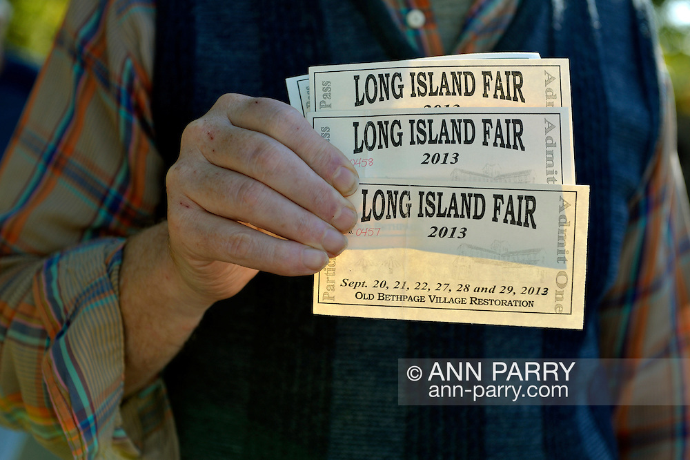 Old Bethpage, New York, U.S. 29th September 2013. Bob Stuhmer holds four admission tickets at The Long Island Fair. A yearly event since 1842, the county fair is now held at a reconstructed fairground at Old Bethpage Village Restoration.