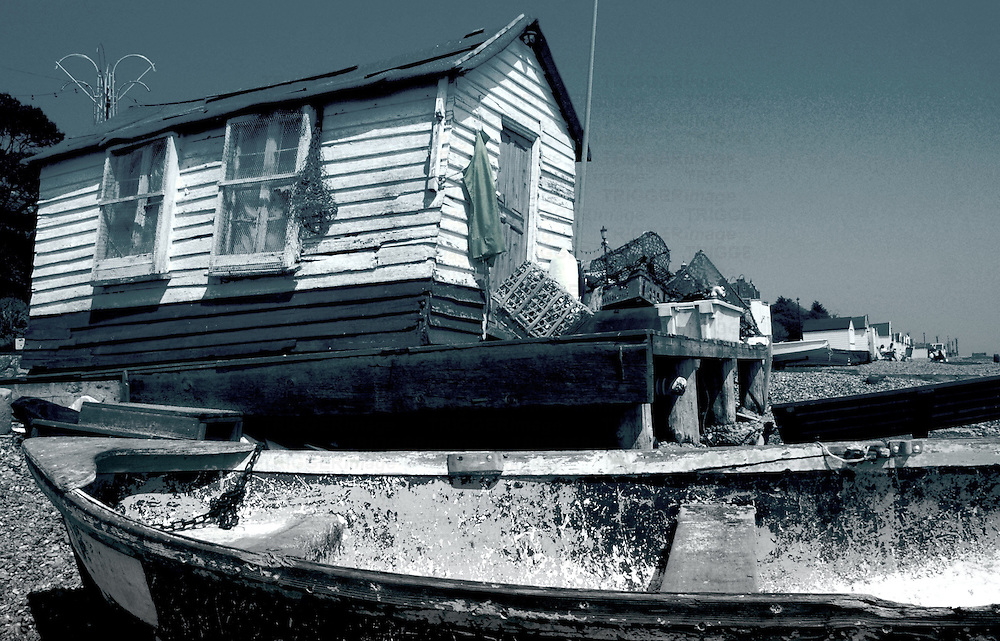 An old fishing boat on a beach next to an old fishermans shed in Felixstowe Suffolk England