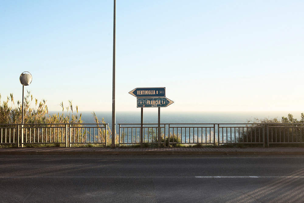 VENTIMIGLIA, ITALY - 17 NOVEMBER 2014: A road sign for Ventimiglia and France is here in Ventimiglia, Italy, on November 16th 2014.<br /> <br /> The Ventimiglia-Menton border is the border between Italy and France crossed by migrants who decide to continue their journey up north towards countries such as Germany, Sweden, The Netherlands and the UK where the process to receive the refugee status or humanitarian protection is smoother and faster. in Ventimiglia, Italy, on November 17th 2014.