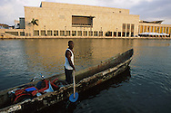 Un hombre rema en un bote, llevando al otro extremo una motocicleta. Al fondo se ve el centro de convenciones de Cartagena, importante centro de reuniones nacional e internacional. Cartagena de Indias, 2001 (Ramón Lepage / Orinoquiaphoto)    The fortified wall of Cartagena is in excellent condition and stretches more-or-less unbroken round a good portion of the Old Town. It is a pleasure for locals well as visitors to walk and observe the colonial architecture and excellent view of the Caribbean ocean..