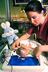Stock photo of a nurse caring for a premature baby.