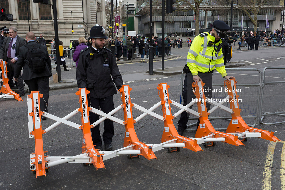Met police officers drag into place anti-terrorism security barriers called 'Pitagone F18', a rapid deployable Hostile Vehicle Mitigation System made by Nottingham-based company Hardstaff, during preparations for Commonwealth Day service at Westminster Abbey, on 9th March 2020, in London, England. Hardstaff Protect is a division of Hardstaff Barriers, a leading supplier of temporary and permanent off-highway barrier protection and zonal delineation solutions.