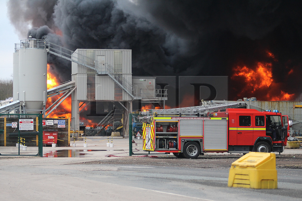 """© Licensed to London News Pictures . 15/03/2015 . Salford , UK . Fire engine at the scene . Roads are closed and people have been evacuated as a large fire burns at a unit within """" Junction Eco-Park """" in Clifton , Greater Manchester , this evening (Sunday 15th March 2015) . The smoke and flames can be seen for many miles . Forty fire fighters are at the scene working to control the blaze . Photo credit : LNP"""