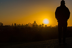 An early morning walker contemplates the view as day breaks over London's skyline, seen from Primrose Hill, to the north of the city. London, November 13 2018.
