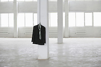 Suit jacket hangs on pillar in empty warehouse