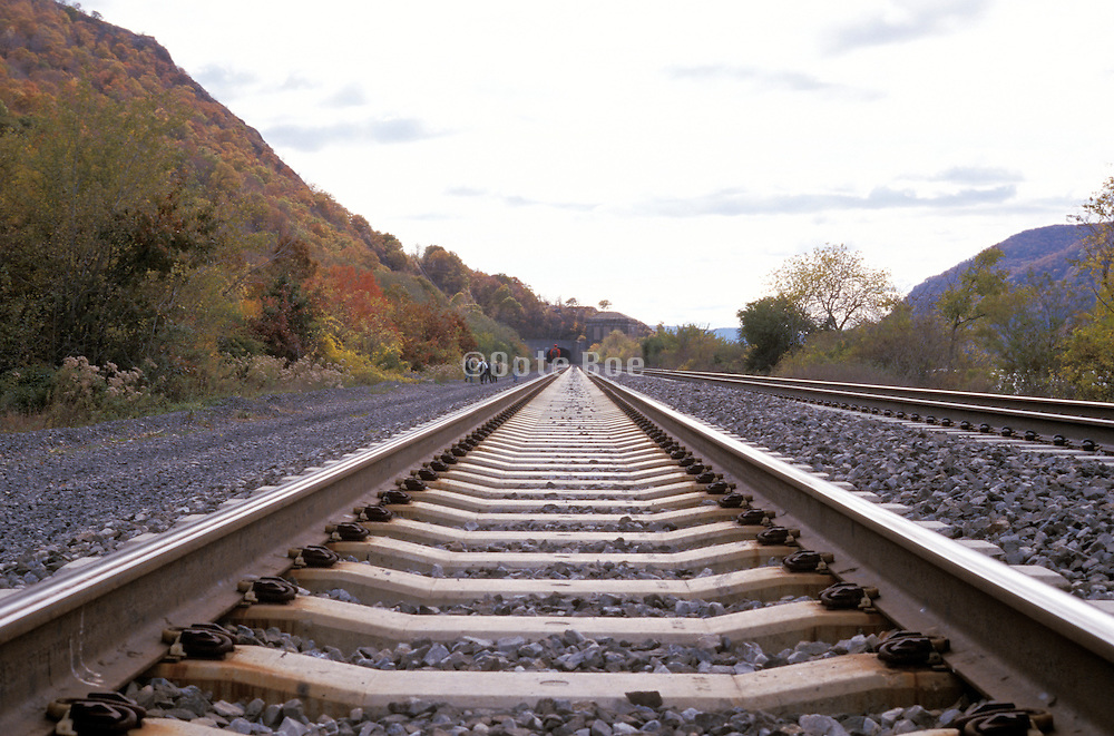 figures walking by train tracks