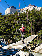 "Hike across a swing bridge beneath The Horns (Los Cuernos) in the the French Valley (Valle Frances) in Torres del Paine National Park, Chile. ""The Horns"" (about 6900 feet or 2100 meters elevation) are a pinkish-white granodiorite intrusion formed 12 million years ago topped with an older crumbly dark sedimentary rock, exposed by freeze-thaw erosion and glaciation. The foot of South America is known as Patagonia, a name derived from coastal giants, Patagão or Patagoni, who were reported by Magellan's 1520s voyage circumnavigating the world and were actually Tehuelche native people who averaged 25 cm (or 10 inches) taller than the Spaniards. For licensing options, please inquire."