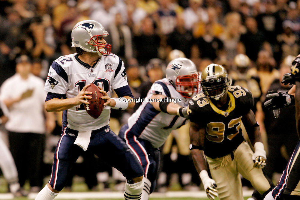 2009 November 30: New England Patriots quarterback Tom Brady (12) is pressured by New Orleans Saints defensive end Bobby McCray (93) during a 38-17 win by the New Orleans Saints over the New England Patriots at the Louisiana Superdome in New Orleans, Louisiana.