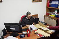 BARCELLONE POZZO DI GOTTO (ME), ITALIA - 20 FEBBRAIO 2015: Don Pippo Insana, fondatore della Casa di Solidarietà e di Accoglienza e attivista contro la chiusura degli OPG, lavora nel suo ufficio, a Barcellona Pozzo di Gotto il 20 febbraio 2015.