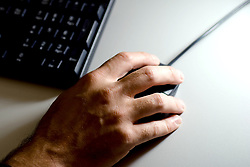"""File photo dated 01/07/08 of a person using a computer mouse. A survey from Nationwide Building Society found that people could be more at risk of falling for an email scam than a more """"traditional"""" con where a rogue trader turns up on their doorstep."""
