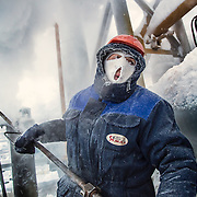 A gas worker in Russia's sub-Arctic Ural region sprays steam on gas condensate pipelines to prevent them from freezing in -42C outdoor temperature.  <br /> <br /> The economic fortune of Russia is largely dependent on the sale of its oil and gas. <br /> <br /> Recent international economic sanctions and fall in energy prices have hurt the Russian economy, sending its currency on a steep descent.