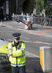 © Licensed to London News Pictures. 05/06/2017. London, UK. A policeman stands near the spot on the southern end of London Bridge where a white van crashed following a terrorist attack in Saturday evening. Three men attacked members of the public  after a white van rammed pedestrians on London Bridge.   Ten people including the three suspected attackers were killed and 48 injured in the attack. Photo credit: Peter Macdiarmid/LNP