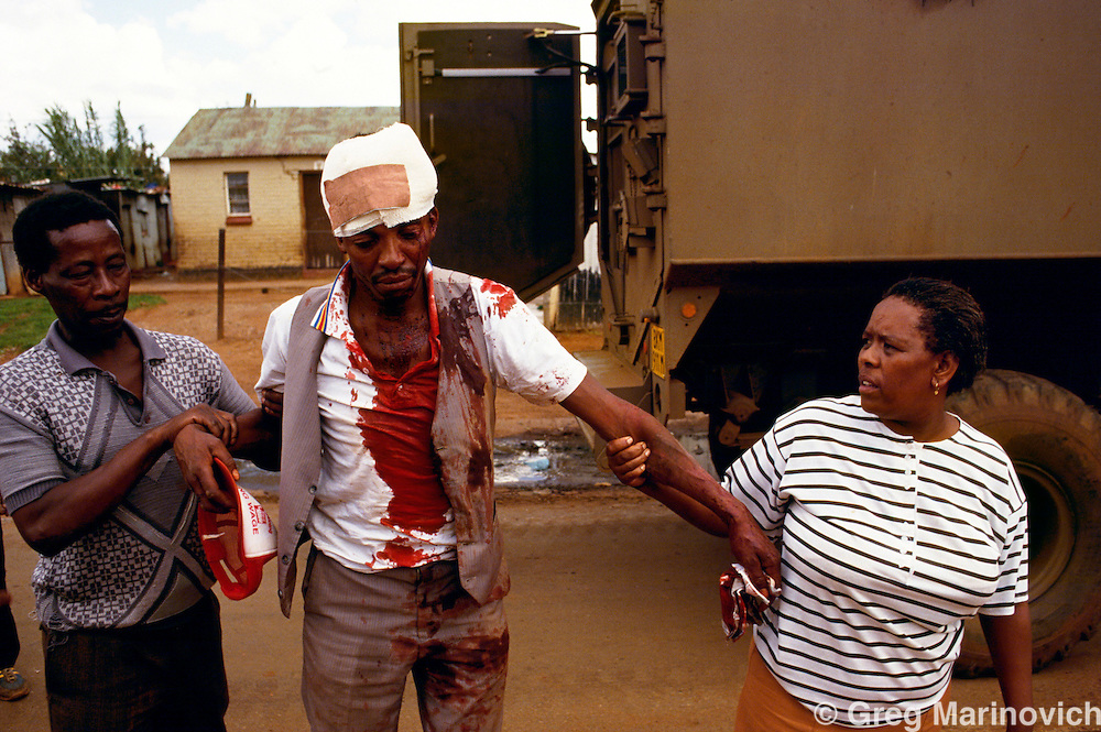 Bekkersdal, Transvaal, South Africa 1994. An injured man is helped away from army treatment during clashes between police, army, Azapo and the ANC is Bekkersdal township, 1994.