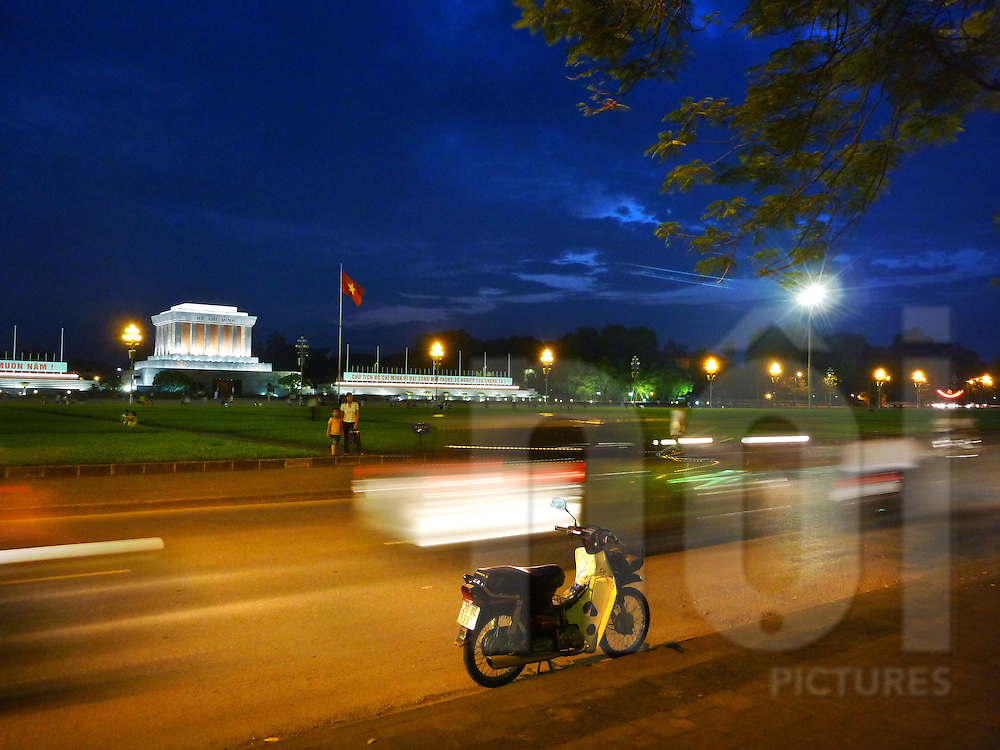 a Honda Dream is parked in front of the Ho Chi Minh Mausoleum at dusk in Hanoi, Vietnam