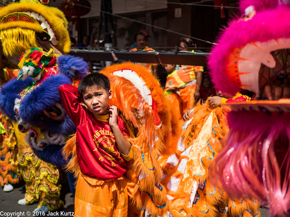 "08 FEBRUARY 2016 - BANGKOK, THAILAND: A child in a Lion dance troupe waits to perform in Bangkok's Chinatown district, during the celebration of the Lunar New Year. Chinese New Year is also called Lunar New Year or Tet (in Vietnamese communities). This year is the ""Year of the Monkey."" Thailand has the largest overseas Chinese population in the world; about 14 percent of Thais are of Chinese ancestry and some Chinese holidays, especially Chinese New Year, are widely celebrated in Thailand.       PHOTO BY JACK KURTZ"