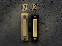 Two apartment doorbell buttons, one black the other silver, mounted to a wall and labeled.