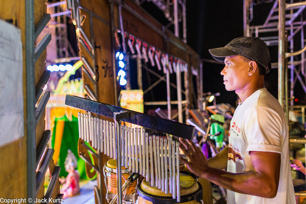 22 NOVEMBER 2013 - BANGKOK, THAILAND: A percussionist with the Prathom Bunteung Silp plays during a show in Bangkok. Mor Lam is a traditional Lao form of song in Laos and Isan (northeast Thailand). It is sometimes compared to American country music, song usually revolve around unrequited love, mor lam and the complexities of rural life. Mor Lam shows are an important part of festivals and fairs in rural Thailand. Mor lam has become very popular in Isan migrant communities in Bangkok. Once performed by bands and singers, live performances are now spectacles, involving several singers, a dance troupe and comedians. The dancers (or hang khreuang) in particular often wear fancy costumes, and singers go through several costume changes in the course of a performance. Prathom Bunteung Silp is one of the best known Mor Lam troupes in Thailand with more than 250 performers and a total crew of almost 300 people. The troupe has been performing for more 55 years. It forms every August and performs through June then breaks for the rainy season.     PHOTO BY JACK KURTZ