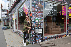 "© licensed to London News Pictures. London, UK 06/08/2012. British singer-songwriter Delilah posing outside the House of Reeves furniture store which was burnt down in last year's riots. The shop has been covered in 4000 images of young people with positive messages on August 6, 2012 in Croydon. The youth volunteering charity ""vInspired"" are marking the one year anniversary of the riots in Croydon by displaying thousands of images of young Britons holding up positive messages about themselves on the House of Reeves furniture store which was destroyed in last year's violence. British singer-songwriter Delilah is one of the supporters of the volunteering charity ""vInspired"". Photo credit: Tolga Akmen/LNP"