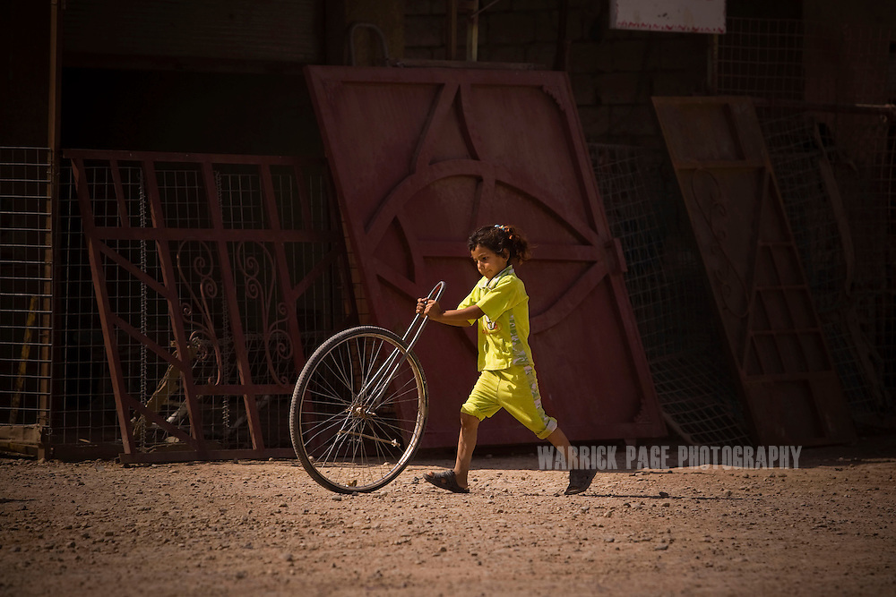ABU GHARMAH, IRAQ - JUNE 10: An Iraqi girl plays with a wheel, on June 10, 2010, in Abu Gharmah, Diyala Province, Iraq. Iraq faces multiple challenges in the lead-up to the drawn-down of US forces in Iraq, with many observers claiming that while they have the capablities of handling home-grown problems, they are far from being able to tackle external threats. Political wrangling has reportedly fostered greater instability throughout the country with fears of renewed sectarian violence breaking out as insurgents set-up attacks in an attempt to exploit vulnerabilities amongst the populace. (Photo by Warrick Page)