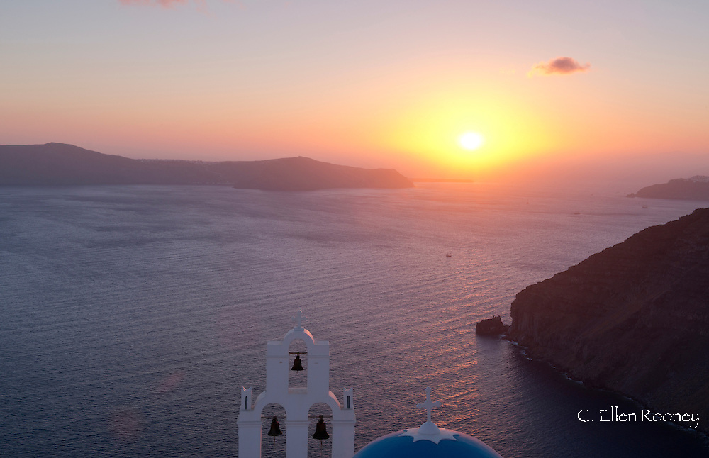 The blue domed Greek Orthodox church overlooking the caldera at sunset at Firostefani,  Santorini, The Cyclades, The Aegean, The Greek Islands, Greece, Europe