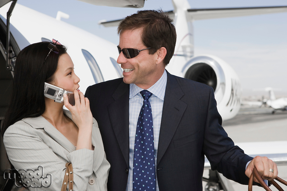 Mid-adult businesswoman and businessman flirting in front of airplane.