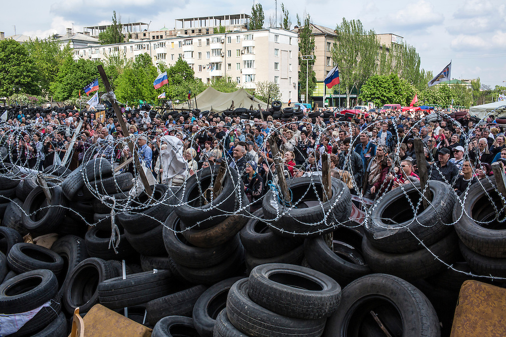 DONETSK, UKRAINE - MAY 4: A crowd of people stands behind barricades outside the regional administration building, which is occupied by pro-Russian protesters, on May 4, 2014 in Donetsk, Ukraine. Cities across Eastern Ukraine have been overtaken by pro-Russian protesters in recent weeks, leading the Ukrainian military to respond with force in some areas. (Photo by Brendan Hoffman for The Washington Post)