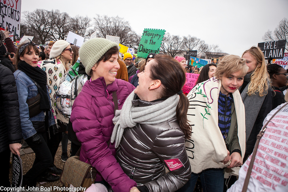 Mary Holland, of Chicago, left, and Caryn Mefford, from St. Louis, embraced as marchers danced and sang in the street to music provided by Sisters of Liberty, on the corner of 7th and Madison, near the National Mall, during the Women's March on Washington where an anticipated 200,000 people turned into an estimated 500,000 to 1 million people, on Saturday, January 21, 2017.  John Boal Photography