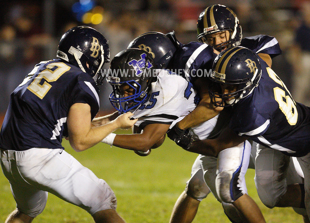 Pine Bush defenders, including Ryan Duggan, at left, and Brendan Watson, at right, tackle Middletown quarterback Kashaun Curry during a game in Pine Bush on Friday, Sept. 27, 2013.