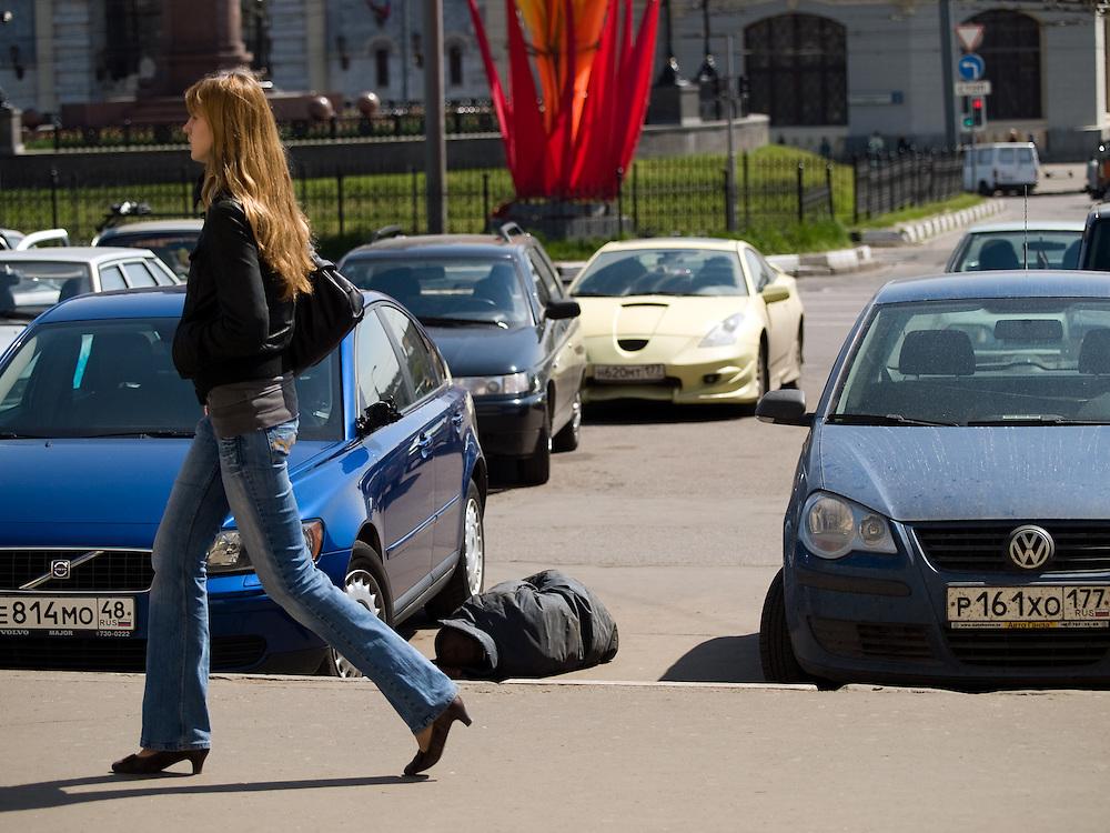 Obdachloser Mann schlaeft auf einem Parkplatz zwischen Autos auf der gegenueberliegenden Strassenseite des Kasaner Bahnhofs (Kasanski woksal) welcher einer der neun Bahnhoefe in Moskau ist. Er liegt am Komsomolskaja-Platz, in unmittelbarer Naehe zum Jaroslawler und dem Leningrader Bahnhof, und ist bis heute einer der groessten Bahnhoefe der russischen Hauptstadt.<br /> <br /> Homeless person is sleeping on a parking place in between cars on the opposite site of the Kazansky Rail Terminal (Kazansky vokzal) which is one of eight rail terminals in Moscow, situated on the Komsomolskaya Square, across the square from the Leningradsky and Yaroslavsky terminals.