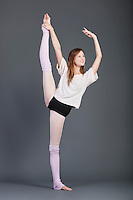 Happy young woman performing ballet over grey background