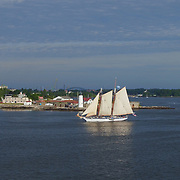 The Harvey Gamage sails past Portsmouth Light House and Fort Constitution at the mouth of  the Piscataqua River off  New Castle, NH during the Parade of Sail event, August, 2016.