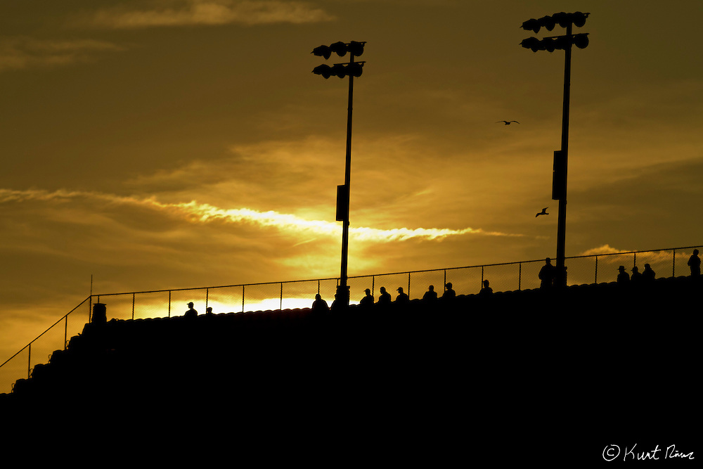 Spectators in the stands as the sun sets during the Rolex 24 Hour Race at Daytona International Speedway in Daytona Beach, FL on January 28, 2012.