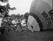 Dew Mighty Minerals Hot Air Balloon.   (H15)..1974..07.08.1974..08.07.1974..7th August 1974..The launching of the Dew Mighty Minerals hot air balloon,took place in Tullamore,Co Offaly last night,as part of the Tullamore Festival Week. The balloon was piloted by Mr Wilf Woollett,a veterinary surgeon from Loughrea,Co Galway and his co-pilot was Kevin Haugh. Miss Rosemary Mannion,the Offaly Rose of Tralee contestant sent the balloon on its way by popping a bottle of Champagne over it.  The balloon itself has a capacity of 56,000 cubic feet,is 60ft high and 50ft wide. It is made from nylon/polyproplene. The basket is 2ft square by 3ft high and carries two people,it is attached to the balloon by steel cables..Wilf Woollett has piloted the balloon in the U.S. and Britain and is a member of the Dublin Balloon Club...As the balloon begins to reach its full size crowds are pictured starting to gather.