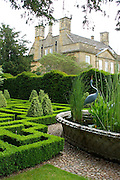 A view of Bourton House from the stunning knot garden. In the centre of the garden is a huge antique basket-weave design pond in raised Cotswold stone. The maze-like beds of the knot garden, precision-cut from box (Buxus sempervirens) are amazingly sharp and regular. At their corners are groups of pyramid topiaries. <br />