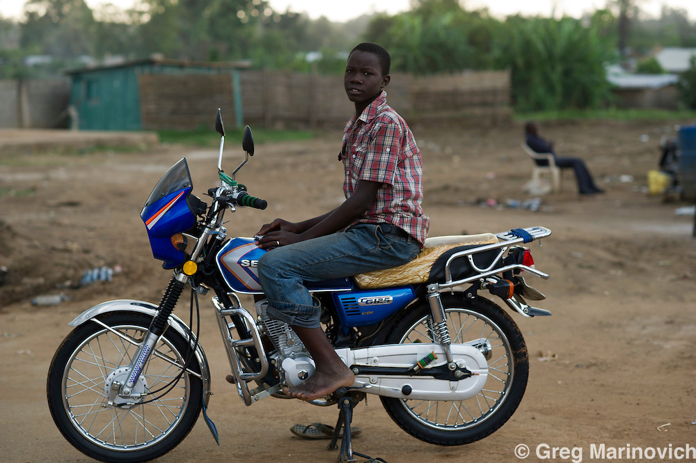 Juba, South Sudan. July 2011. Nicolas Rwaga, 16, a Ugandan orphan who has come to seek work in Juba, washes motorbikes for USD 0.30 a bike. On July 9, 2011, South Sudan became the 54th African state and the first to break with colonial era boundries as it gained it independence from Sudan, dominated by the Muslim north, following a thirty year war. South Sudan is predominantly Christian, and has access to vast oil wealth, yet the war and continued small scale conflicts keep the vast majority living in poverty and hunger. Photo Greg Marinovich / Storytaxi.com