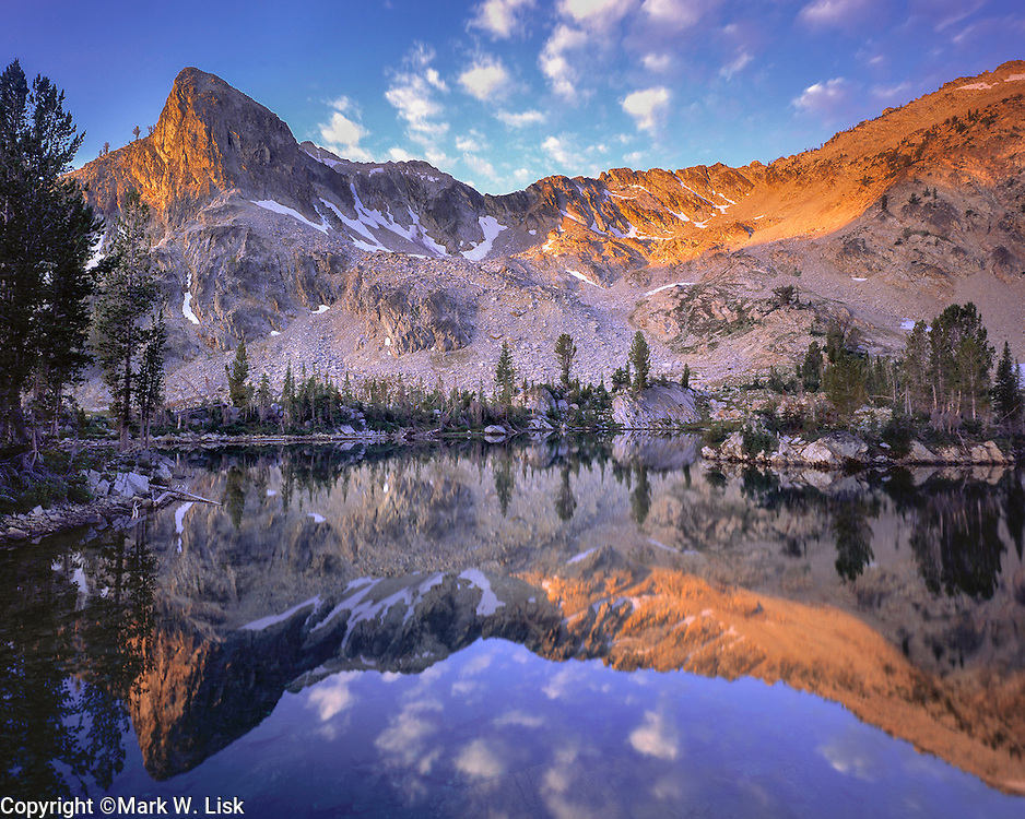 Rugged Sawtooth peaks and cotton like clouds reflect in Twin Lake.