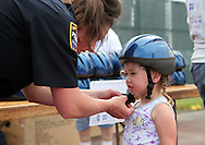 Cedar Rapids Police Officer Shannon Stokesberry (from left) helps adjust a bike helmet for Gabby Wickham, 3, of Cedar Rapids at the 21st annual Tanager Place Summer Fest at the Rockwell Collins Sports Complex in Cedar Rapids on Saturday afternoon, June 4, 2011. St. Luke's Hospital gave away 1,000 bike helmet. Activities included the General Mills Make-Your-Own Cereal Tent, miniature golf, Video Game Etc tent, forty free kids' crafts and displays, a car show, and music. All proceeds from the event went to Tanager Place.