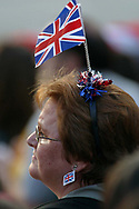 A woman with patriotic accessories watches a broadcast of a rock concert held in Buckingham Palace's grounds to celebrate Queen Elizabeth II's Golden Jubilee. Celebrations took place across the United Kingdom with the centrepiece a parade and fireworks at Buckingham Palace, the Queen's London residency. Queen Elizabeth ascended to the British throne in 1952 upon the death of her father, King George VI.