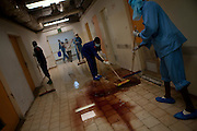 Workers at an abandoned Abu- Salem hospital  in Tripoli  mop up the blood where bodies were found decomposing . In one of the hospital rooms, evidence indicates that an execution took place .(Photo by Heidi Levine/Sipa Press).
