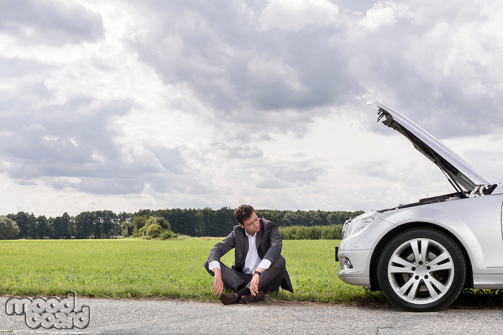 Full length of worried businessman sitting by broken down car at countryside