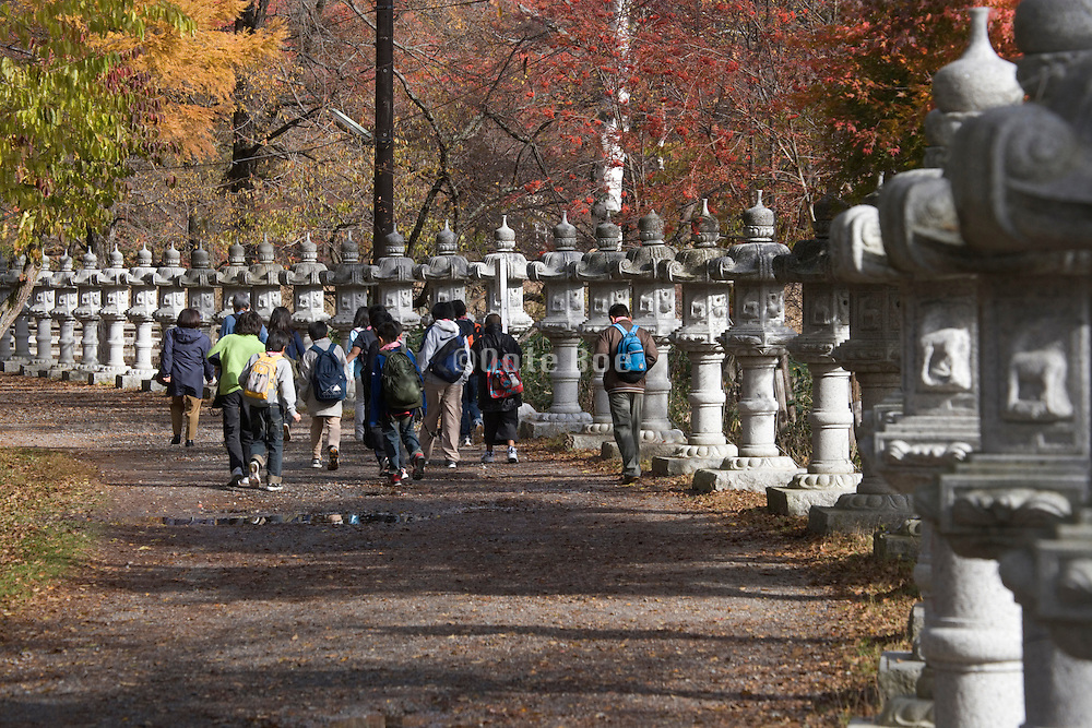 children walking on a rural road lined with stone toro lanterns Japan